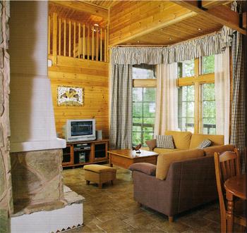 Палитра интерьера построена на сочетании теплых и холодных оттенков. Белая облицовка кожуха и дымохода камина, черно-белые занавески и бежево-сиреневый диван удачно смотрятся на фоне янтарных стен
